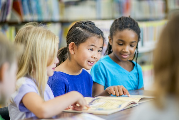 A group of elementary school girls of different ethnicity are indoors in their school library. They are sitting together at a table and reading together.
