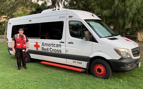 Timothy Duston standing in front of the Red Cross van