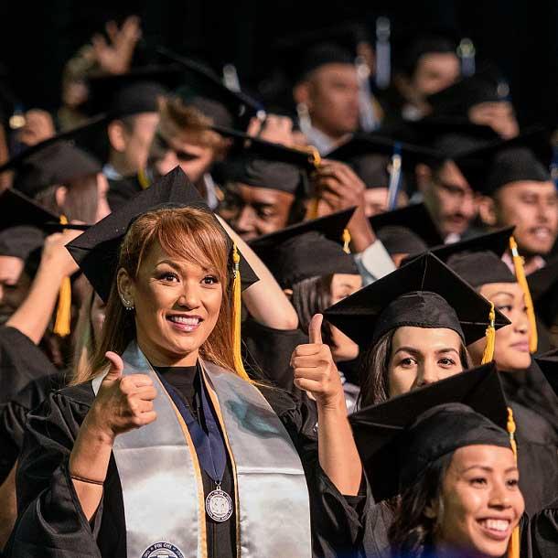 Chaminade University graduate smiling at camera and giving the thumbs up