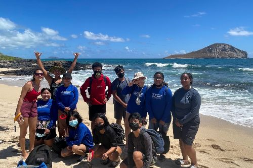 high school students at the beach looking at marine life during the marine science summer institute