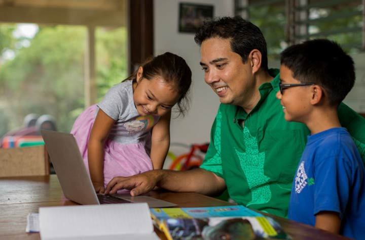 Dad with two children doing online learning