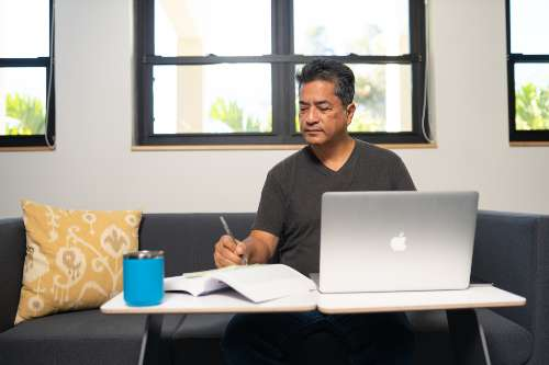 An online undergraduate student does his class assignment on his laptop
