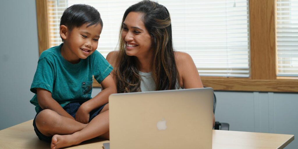 A Chaminade online undergraduate student works on her homework as her son looks at her laptop